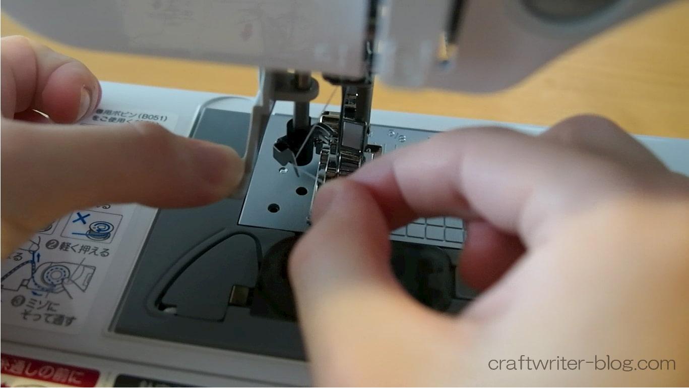 押えレバーを下げて糸通し機で針に糸を通す