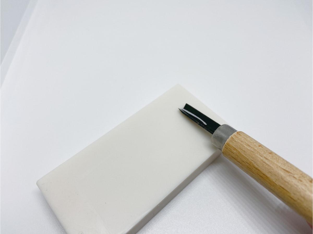 三角刀の彫刻刀で消しゴムを彫る様子