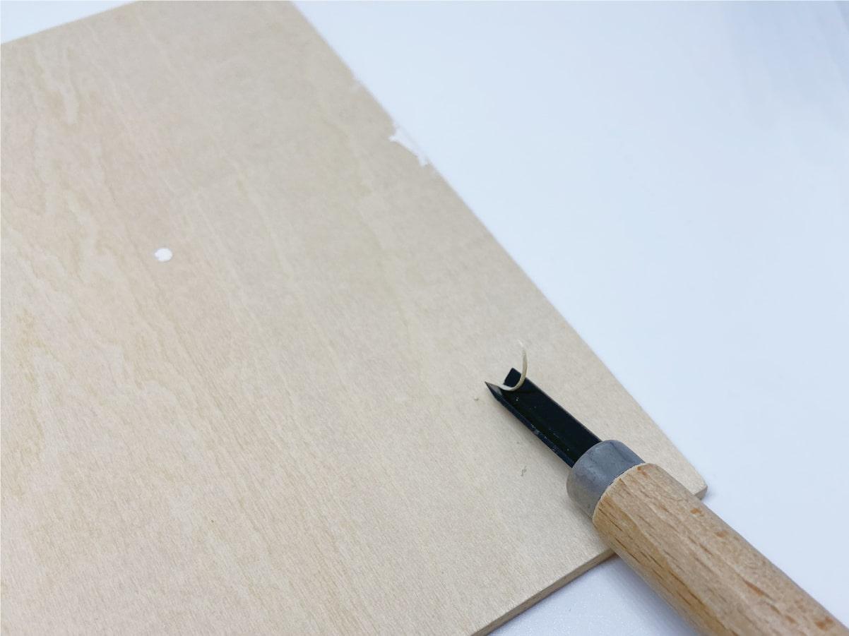 三角刀の彫刻刀で木を彫る様子