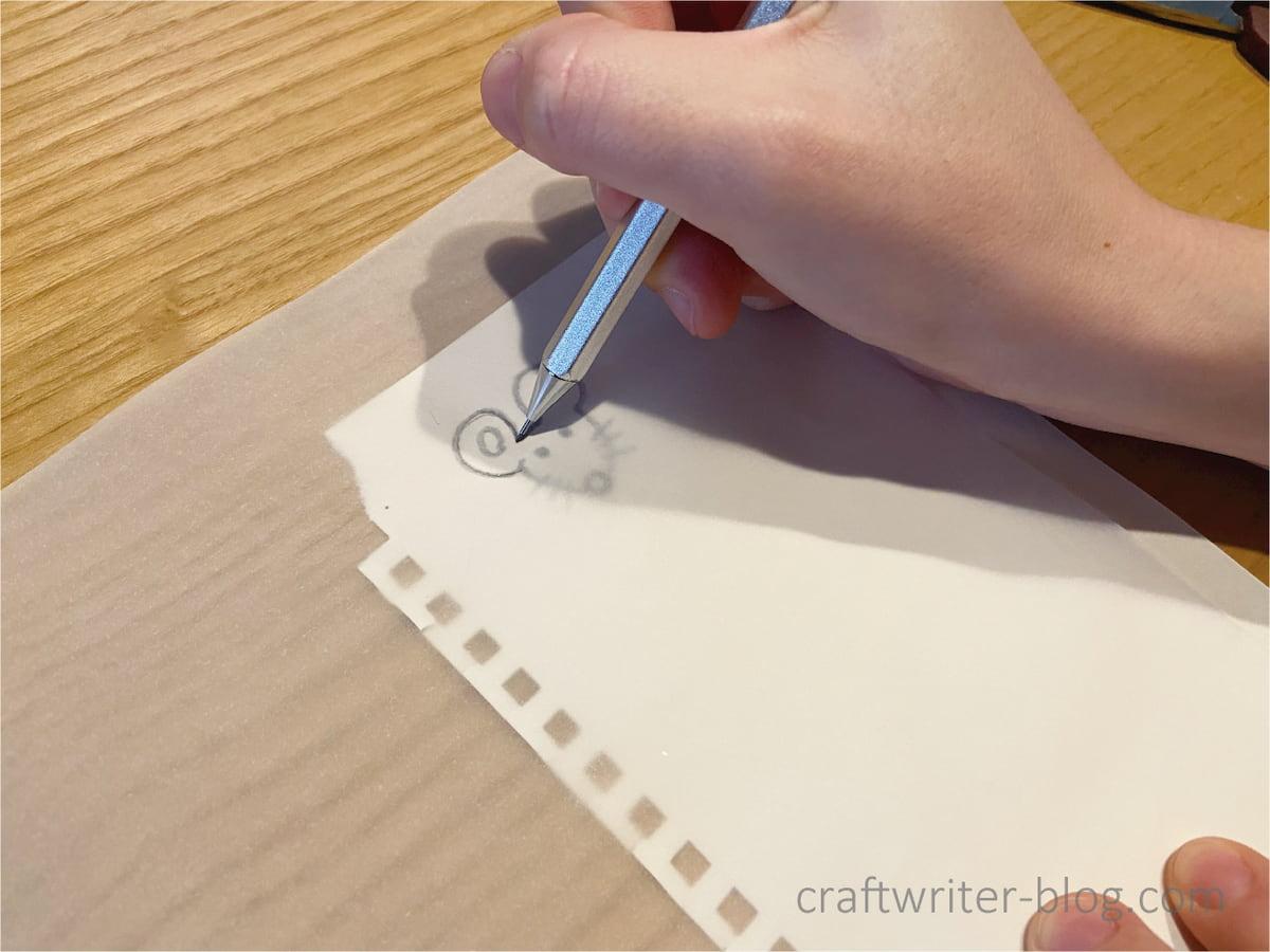消しゴムはんこのネズミの図案をトレーシングペーパーに写す作業